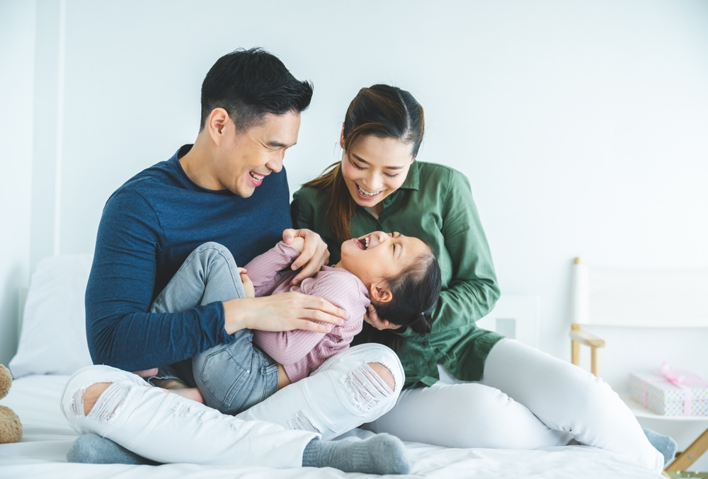 Happy Family Laughing and Playing With Daughter